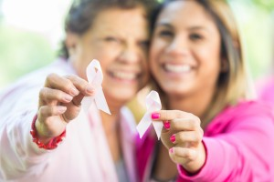 Hispanic women holding breast cancer awareness ribbons