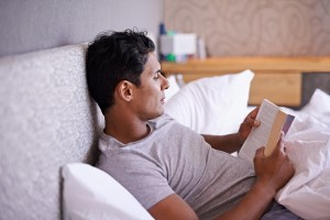 Latin man reading book in bed