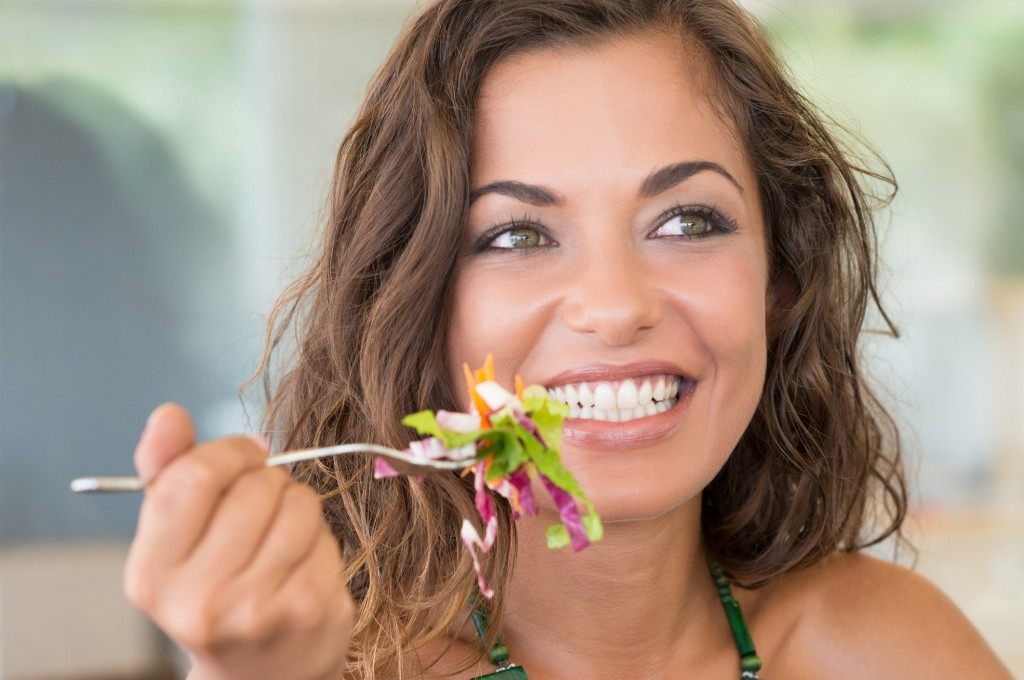 Smiling Woman on a diet eating healthy