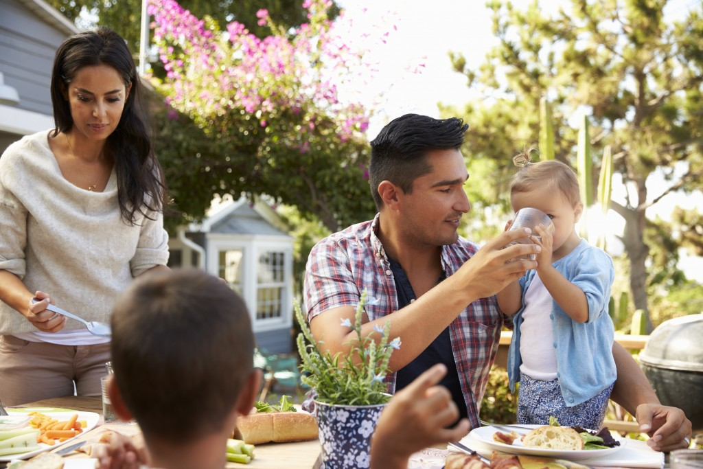 Hispanic Family At Home Eating Healthy Meal in Garden